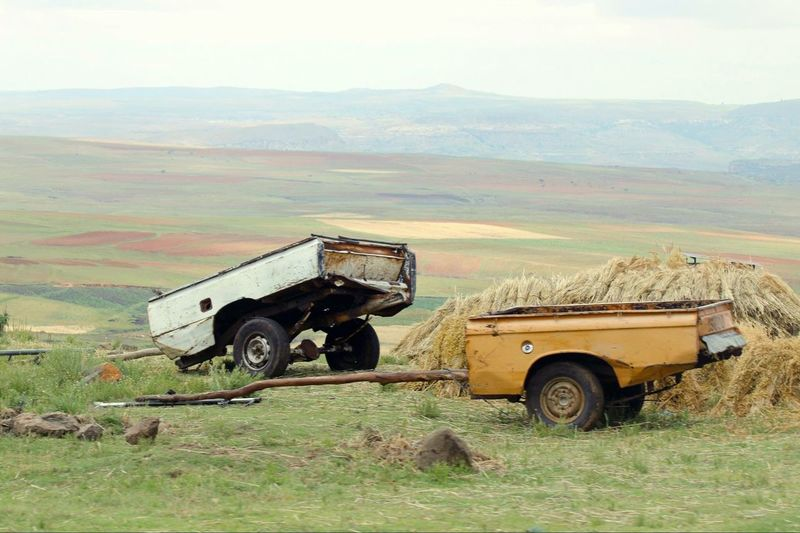 Pick-up truck on grassy field against sky