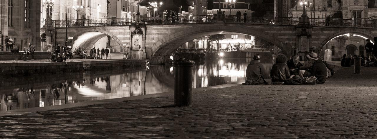 People sitting on illuminated bridge in city