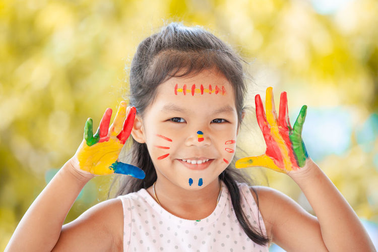Close-up portrait of smiling girl with body paints gesturing