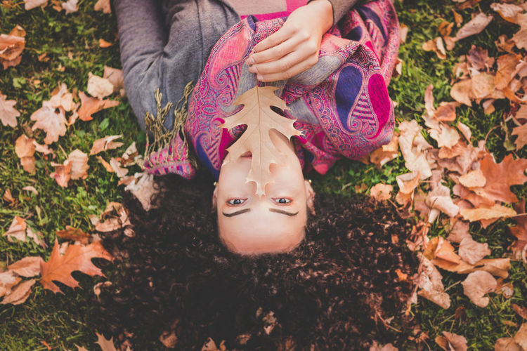 High Angle Portrait Of Young Woman Lying On Field At Park During Autumn