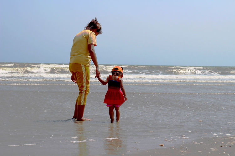 Rear view of mother and daughter standing at beach against clear sky