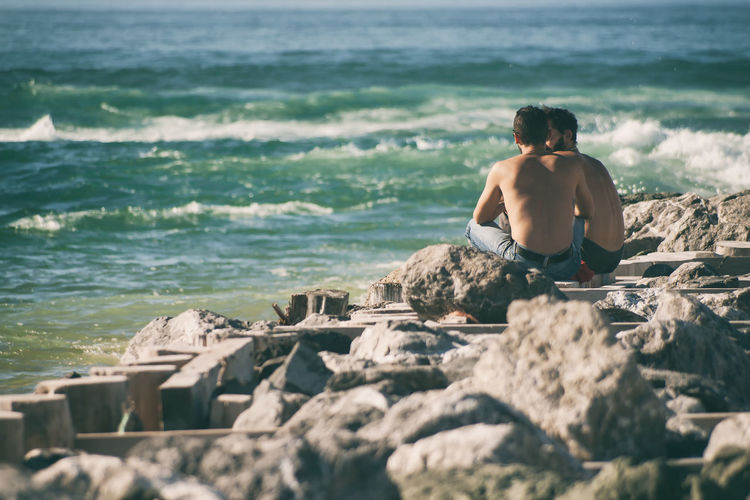 Rear view of man relaxing at beach