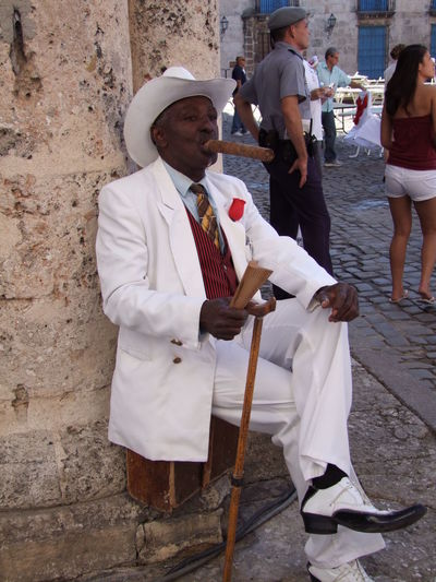Cuban Dandy Alone Casual Clothing Cuba, Havana, Dandy, Man, Cigar, Hat, White, Suit, Shoes Enjoyment Friendship Front View Full Length Leisure Activity Men Occupation Perspective Real People Sitting Togetherness