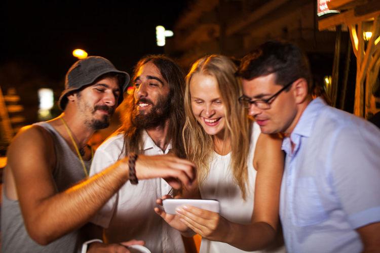 Cheerful friends using phone at night