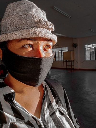 Close-up of cute girl wearing flu mask looking away standing indoors