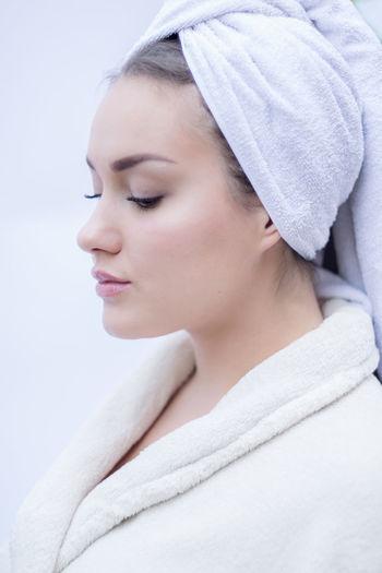 Close-Up Of Teenage Girl Wearing Bathrobe Against White Background