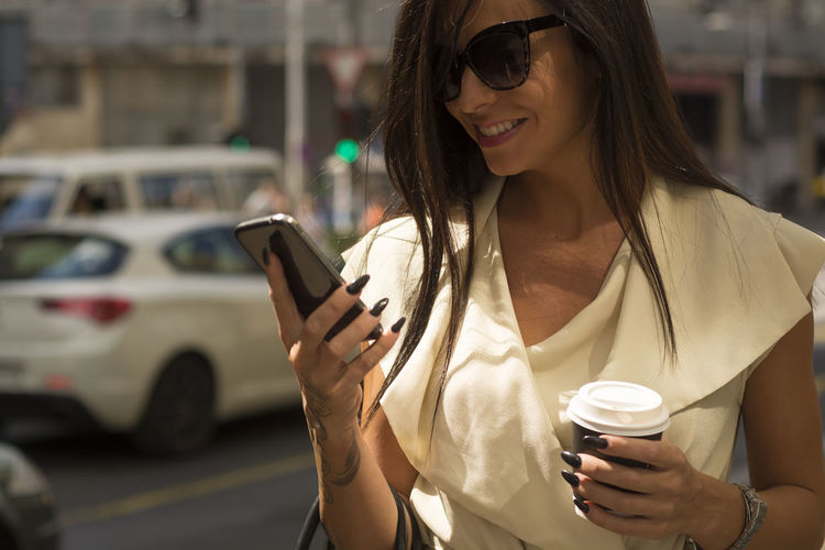 Woman looking at mobile phone in city