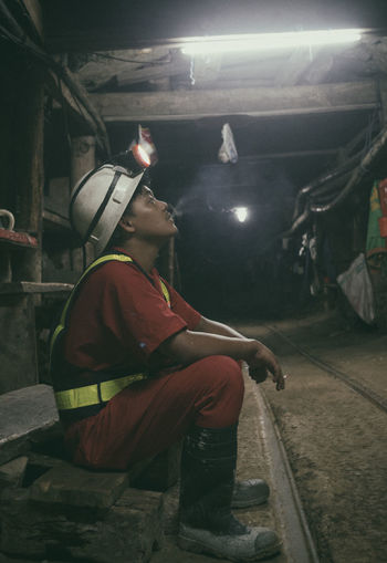 Side view of worker smoking cigarette while sitting underground tunnel