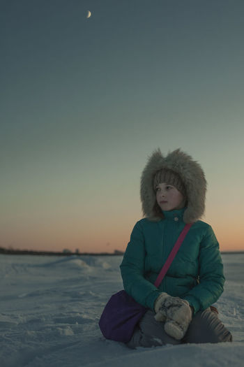 Portrait of woman sitting on snow against sky during sunset