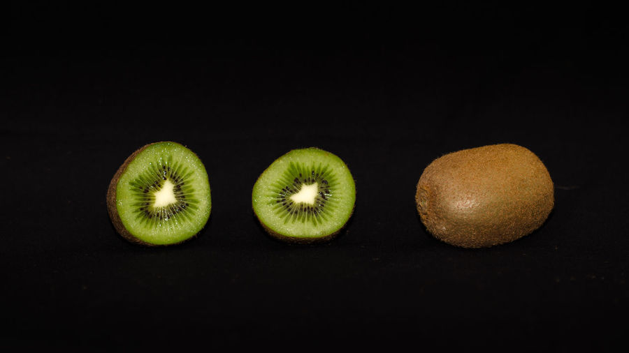 Close-Up Of Kiwis Against Black Background
