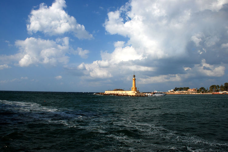 View Of Lighthouse In Sea Against Cloudy Sky