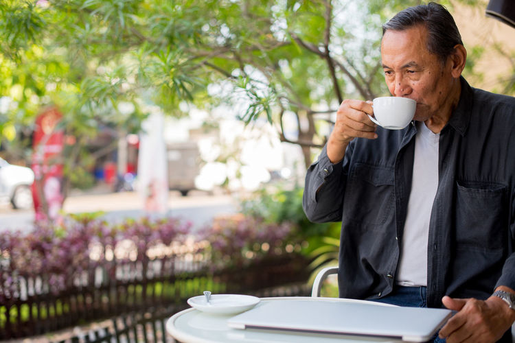 Adult Cafe Coffee - Drink Coffee Break Coffee Cup Cup Day Drink Drinking Food And Drink Freshness Holding Mature Adult Men One Man Only One Person Only Men Outdoors People Refreshment Relaxation Sidewalk Cafe Sitting Table Tree