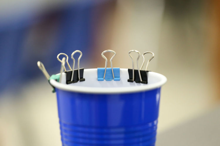 Close-up of paper binders on drinking glass