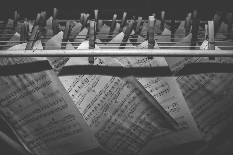 Close-Up Of Music Sheets Hanging On Metal Rods