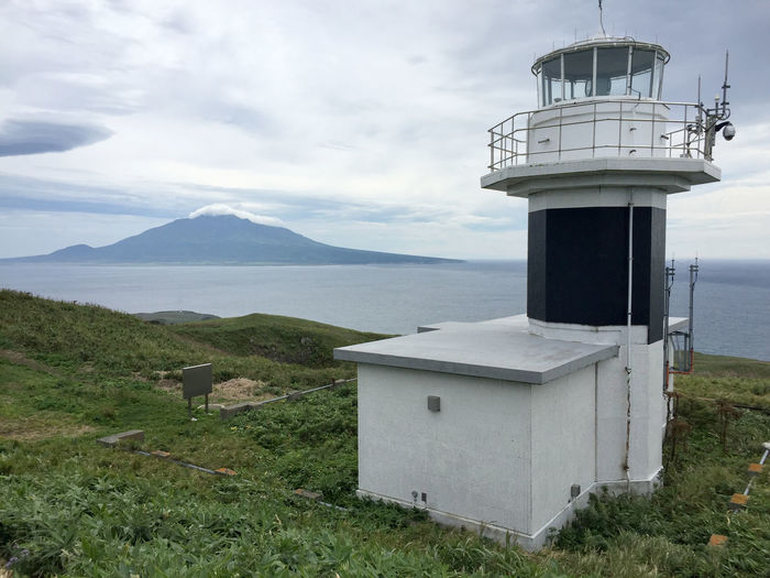 Hokkaido Lighthouse Rebun Island Rishiri Island Architecture Beauty In Nature Building Building Exterior Built Structure Cloud - Sky Day Environment Grass Guidance Land Mountain Nature No People Outdoors Safety Scenics - Nature Security Sky Tower Water