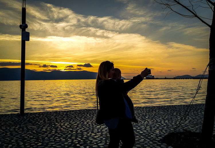 Woman taking selfie with daughter while standing on pier over sea