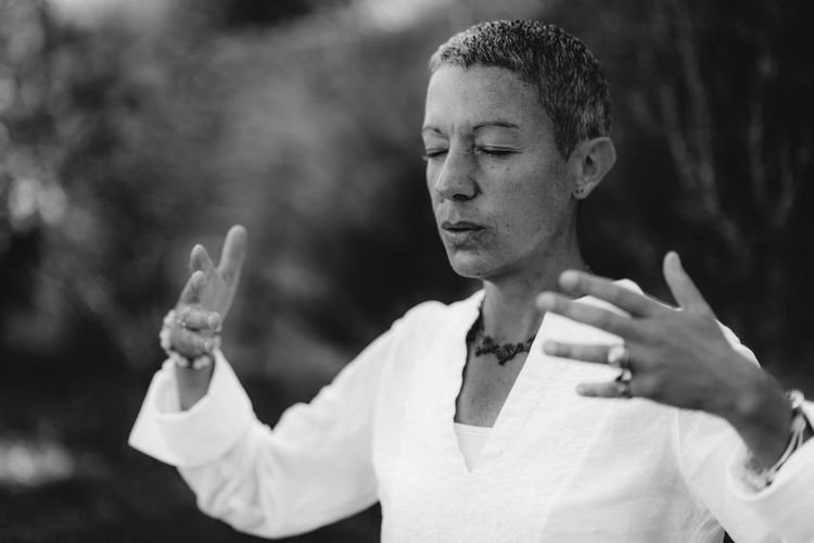 Spiritual coach sending positive thoughts hand gesture