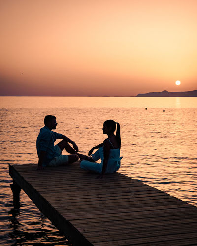 Couple sitting on sea against sky during sunset