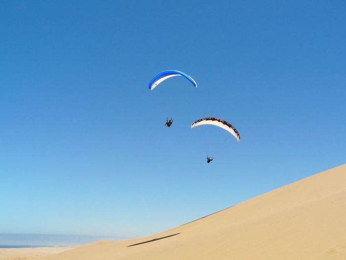 Two people paragliding on landscape against clear blue sky