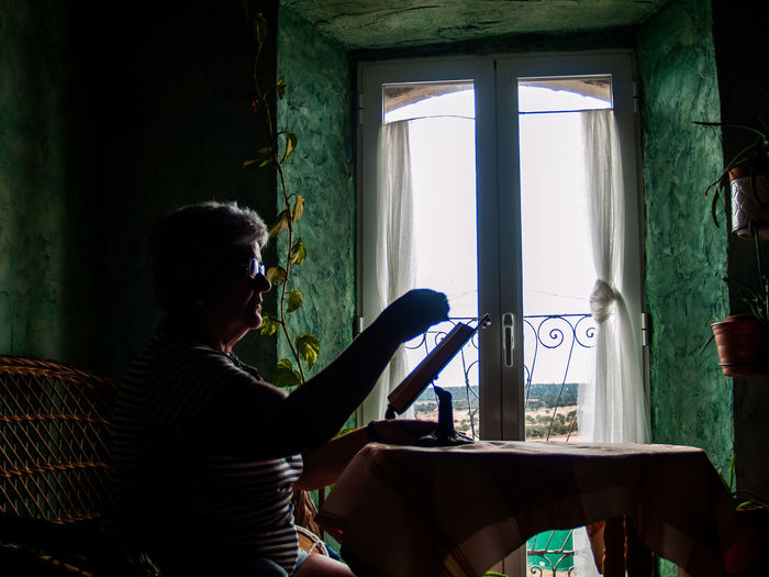 Woman reading book while sitting by window at home