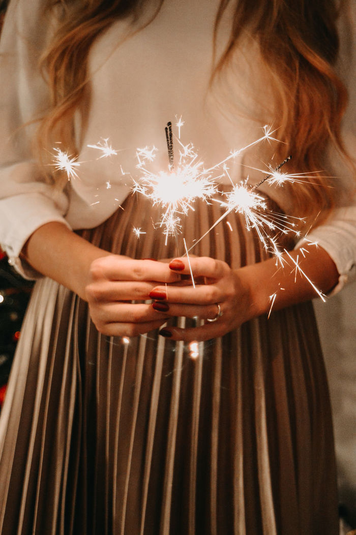 Midsection of woman holding sparklers