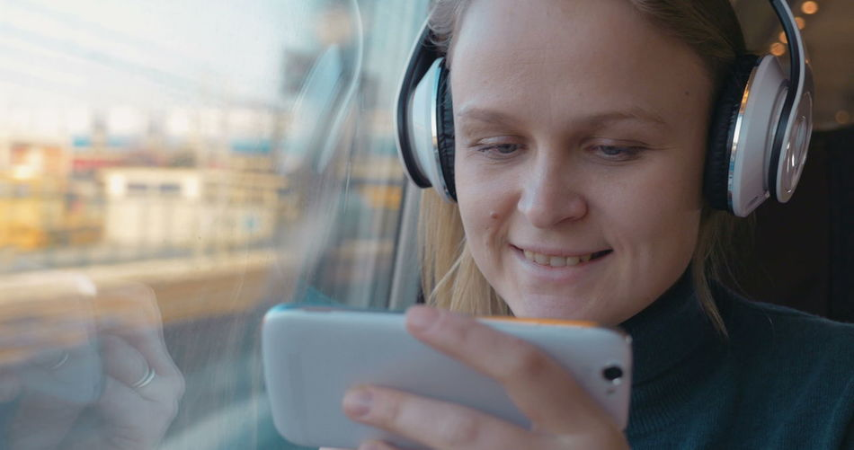 Portrait of smiling woman using mobile phone in bus