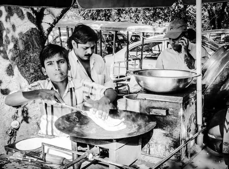 """Chole Kulche - The oh so famous anytime quick calories ; """"I work to fulfill my dreams, do you?"""" These hawkers are a small family oriented business models you will find on the streets of Delhi and around. Bnw Day Food Hawkers Mobilephotography Monochrome People Real People Samsungnote4 Skill  Street Photography Streetphoto_bw Two People Young Adult"""
