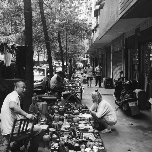 People sitting at market against buildings in city