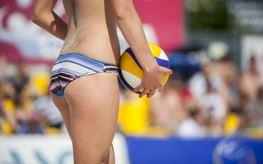 Midsection of woman playing with ball at beach