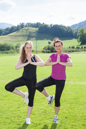 Full Length Portrait of Two Smiling Women Wearing Exercise Clothing Standing Side by Side in Vriksasana Yoga Tree Pose in Sunny Green Field Meditation Yoga Balancing Buddhism Day Fitness Friendship Full Length Grass Healthy Lifestyle Leisure Activity Lifestyles Mental Nature Outdoors Real People Smiling Sports Sports Clothing Standing Teenage Girls Togetherness Two People Young Adult Young Women
