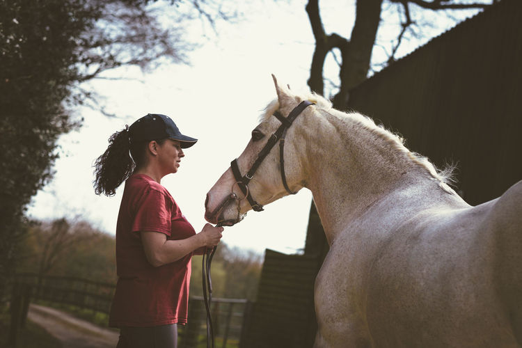 Side view of mature woman standing with horse at barn