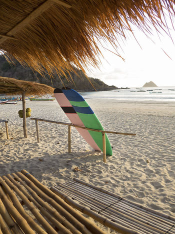 2 surfboards in pastel colors leaning on a bamboo fence on the beach Beach Life Lombok-Indonesia Surf Boards Surfer Baech House Bamboo - Material Bamboo Fence Beac Hut Beach Beachlife No People Pastel Colors Pelican Beach Sand Sea Shore Straw Huts Surf Boards Posca Art Zantangle Surfing Water