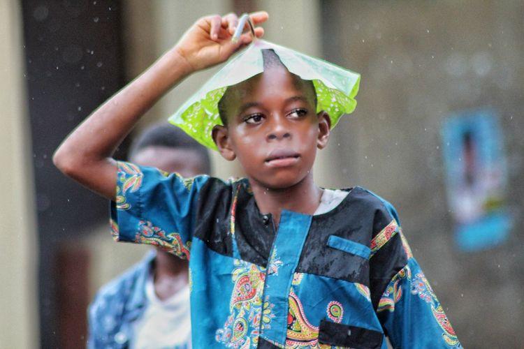Boy covering head with leaf during rainy season