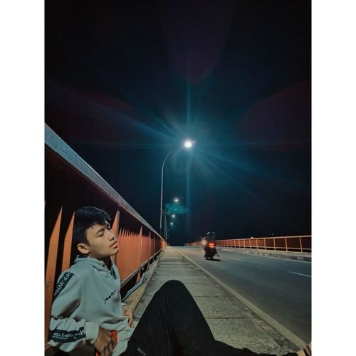 Boy standing on illuminated street at night