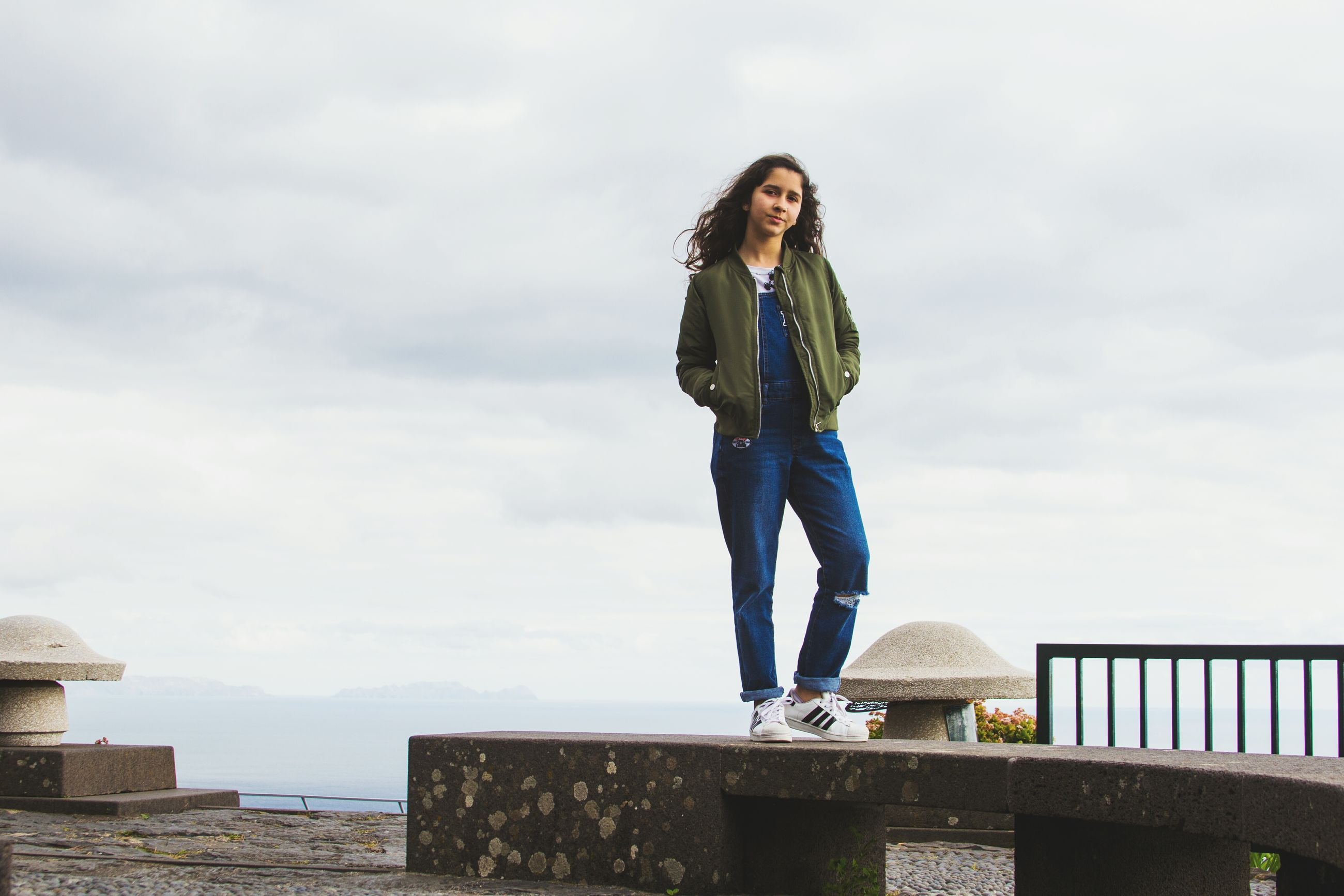 full length, low angle view, sky, one person, cloud - sky, leisure activity, casual clothing, front view, day, one woman only, young women, real people, young adult, looking down, outdoors, only women, one young woman only, beautiful woman, people, adult, adults only