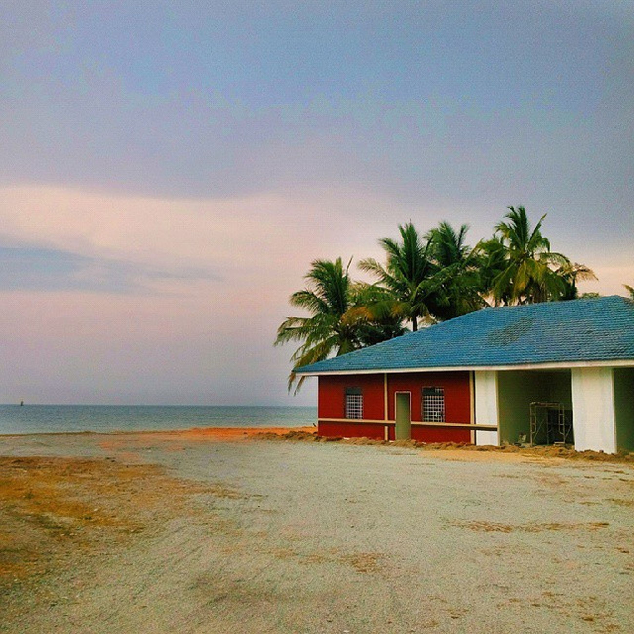 palm tree, sea, beach, sky, horizon over water, built structure, tree, building exterior, water, architecture, shore, house, tranquil scene, sand, tranquility, nature, scenics, beauty in nature, sunset, cloud - sky