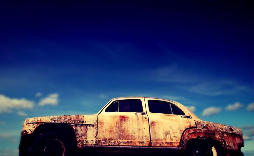 Low Angle View Of Abandoned Rusty Car Against Blue Sky