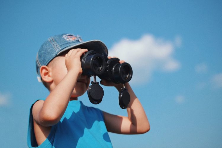 Low Angle View Of Boy Looking Through Binoculars While Standing Against Sky