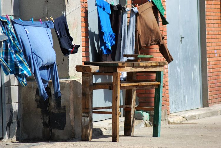 Clothes drying on string by wooden table outside house