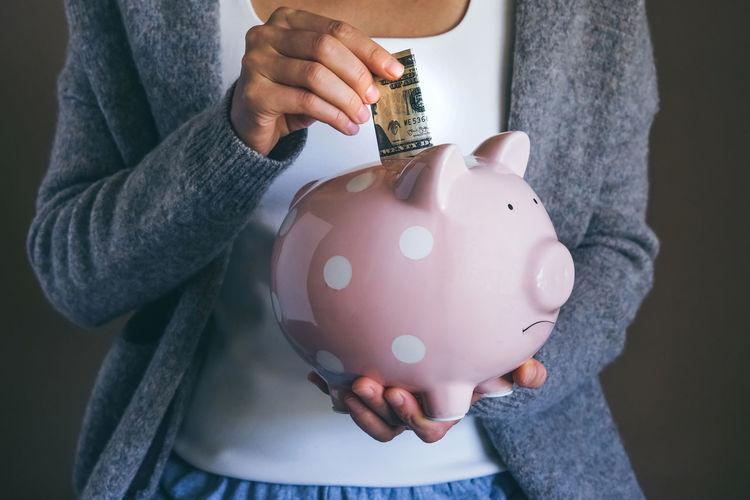 Woman putting bill in sad piggy bank. female saving money. economic crisis concept