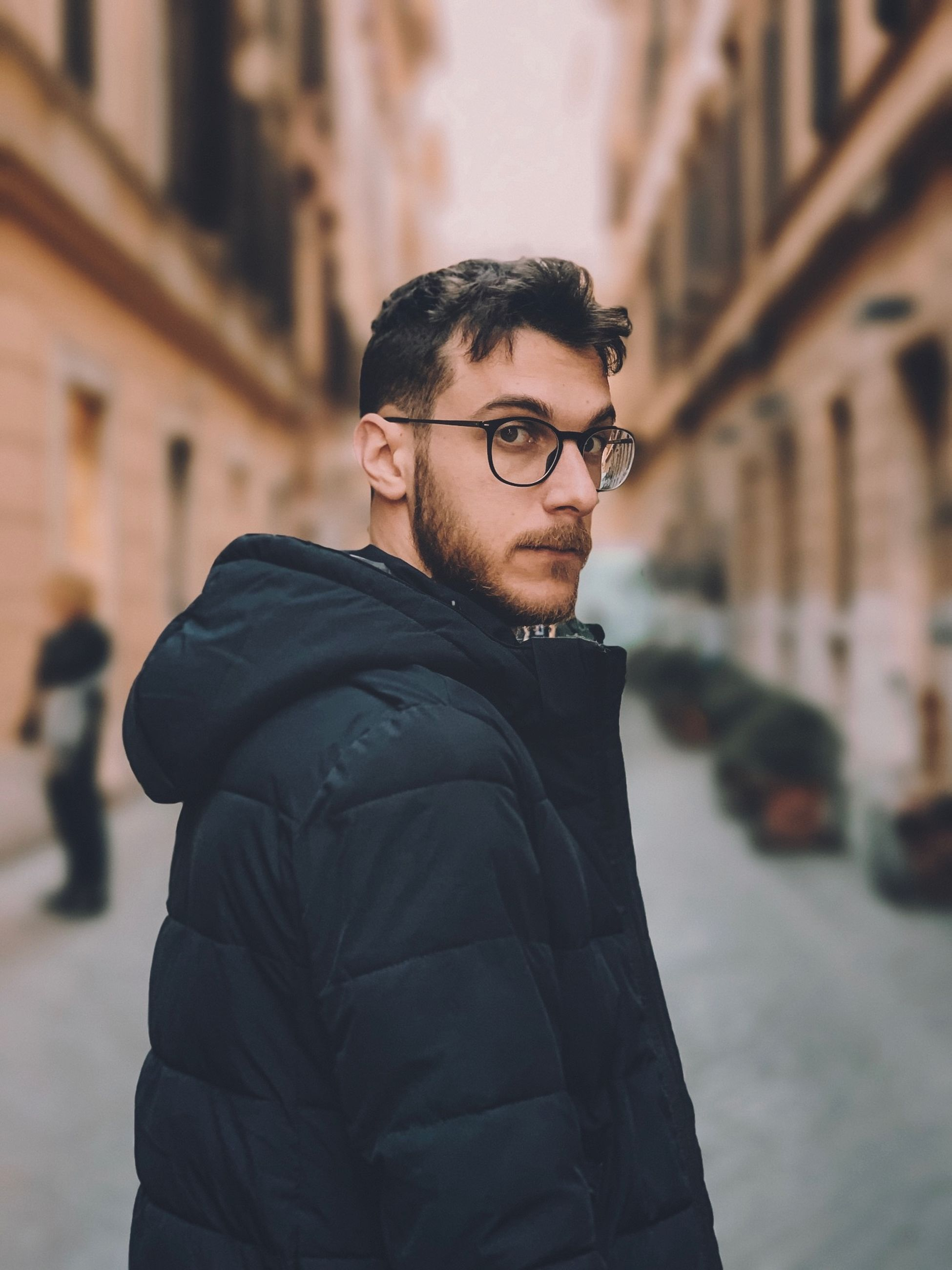one person, eyeglasses, glasses, focus on foreground, young adult, architecture, standing, real people, built structure, clothing, waist up, men, lifestyles, looking at camera, young men, side view, portrait, city