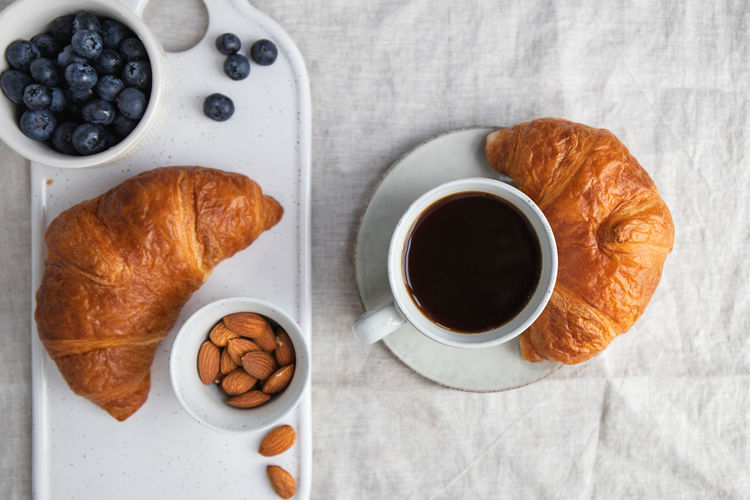 Cup of black coffee with croissant on table. The concept of breakfast, flat lay, top view. Coffee Croissant Breakfast Morning Cup Cappuccino Background Drink Top Pastry Table Latte Cafe Espresso White Hot Americano View Caffeine Bread Food Dessert Fresh Brown Rustic Break Linen Minimalist Minimal Cotton Beige Golden Atmosphere Sweet Above Flat Lay Composition Ceramics Mug Black Milk Cream Beverage Time