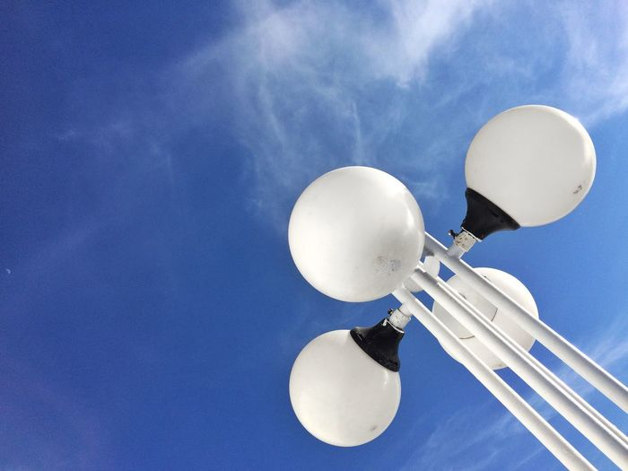 Low angle view of lighting equipment against blue sky