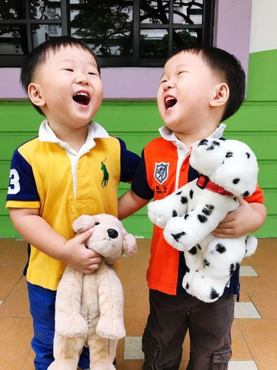 Cute Twins Smiling With Stuffed Toys On Against House
