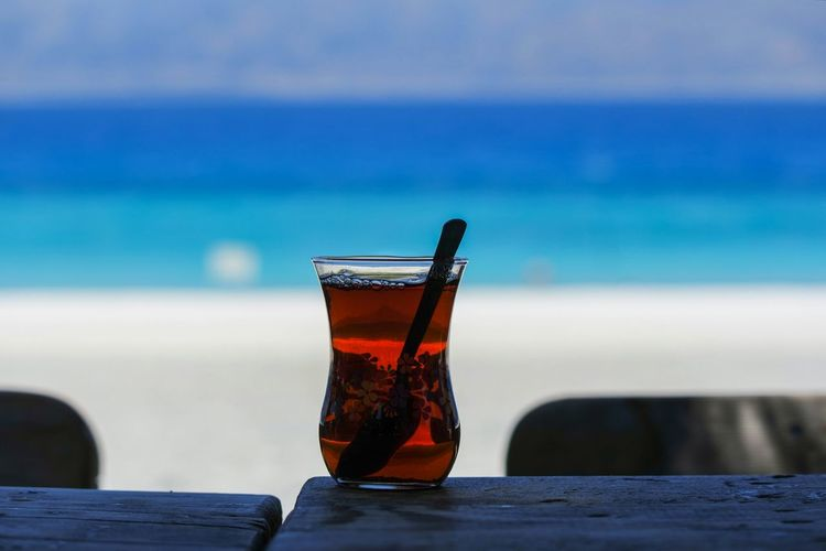 Close-up of drink on table at beach against blue sky