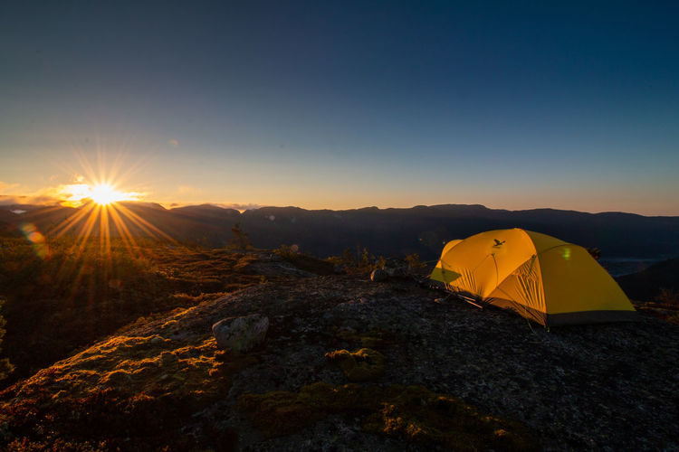 amazing sunrise after a cold night in telemark, norway Camping Holiday Adventure Amazing Beauty In Nature Camping Copy Space Environment Lens Flare Mountain Mountain Peak Nature No People Non-urban Scene Orange Color Outdoors Scenics - Nature Sky Sun Sunlight Sunset Tent Tranquil Scene Tranquility Yellow