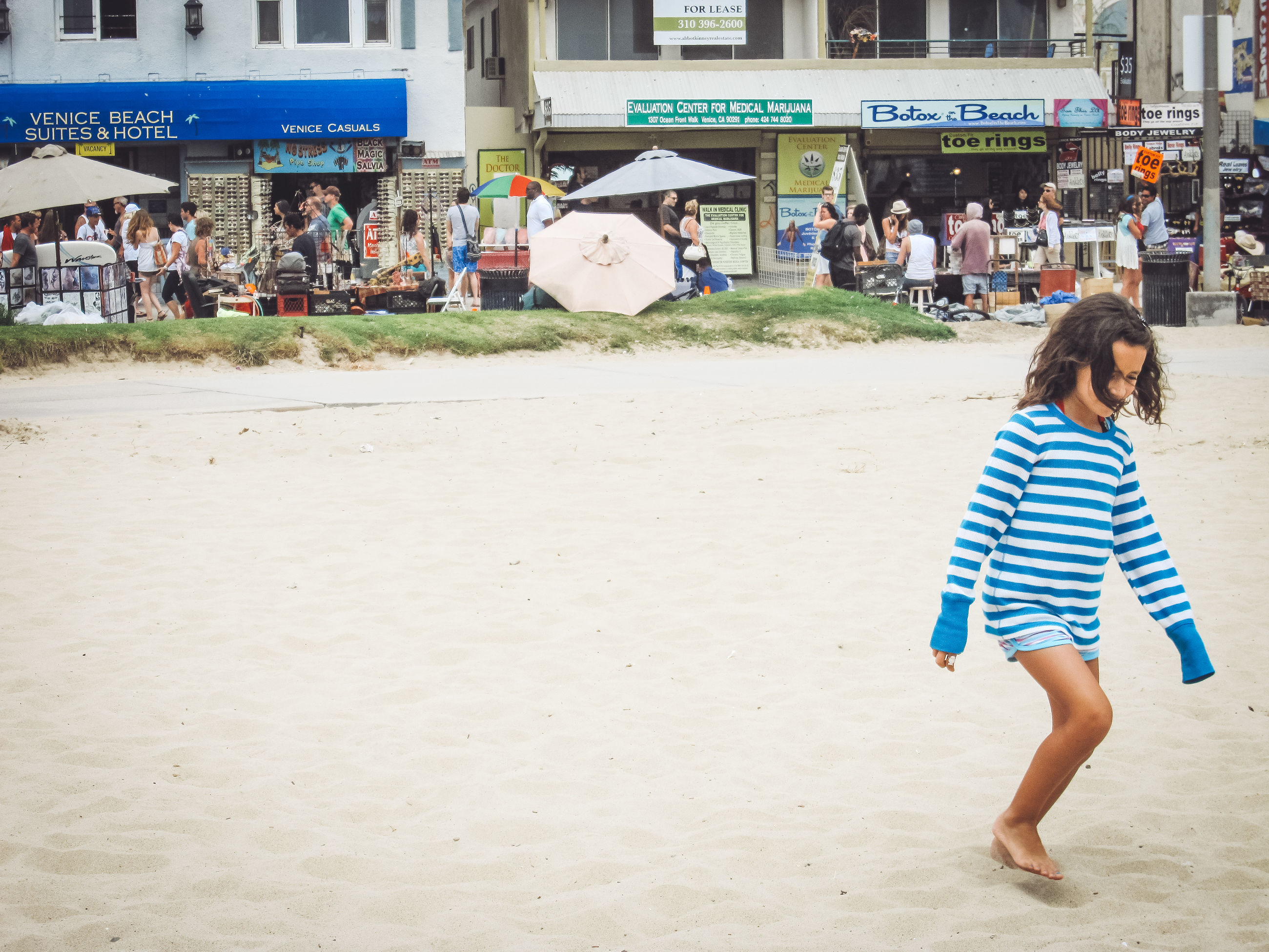 real people, land, one person, women, lifestyles, beach, incidental people, full length, leisure activity, striped, walking, day, girls, sand, casual clothing, architecture, child, city, rear view, outdoors, hairstyle
