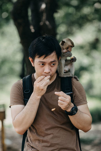 Man with monkey sitting on shoulder
