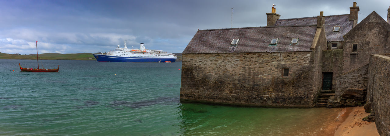 Boats moored on sea against buildings