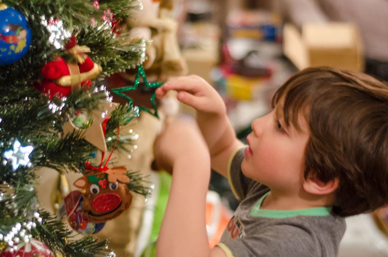 Young boy decorating a Christmas tree 5 Year Old Boy Celebration Child Childhood Christmas Christmas Decoration Christmas Ornament Christmas Tree Close-up Cultures Day Decortation Focus On Foreground Hanging Headshot Holding Holiday - Event Home Interior Indoors  One Person Real People Seasonal Side View Tradition